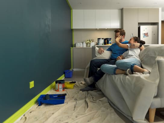 A couple in their rental apartment sitting on a couch resting after painting their lounge room wall